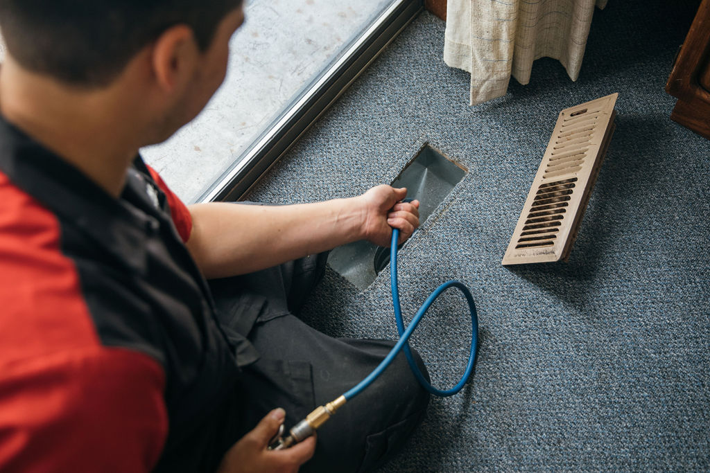 HVAC technician from Capital Heating & Cooling cleaning an air vent.